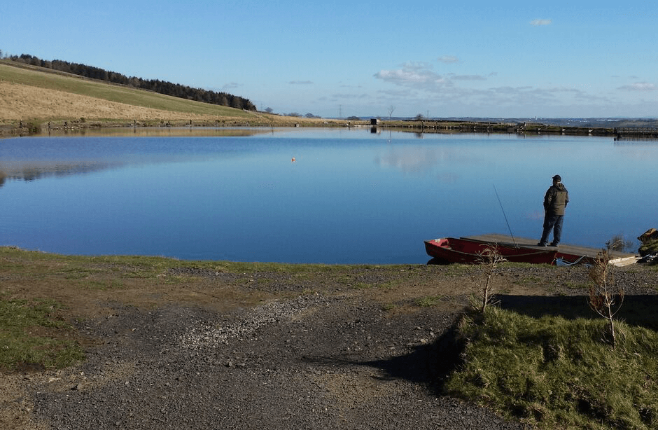 Image of the lake at Woodburn Fishery on a sunny day