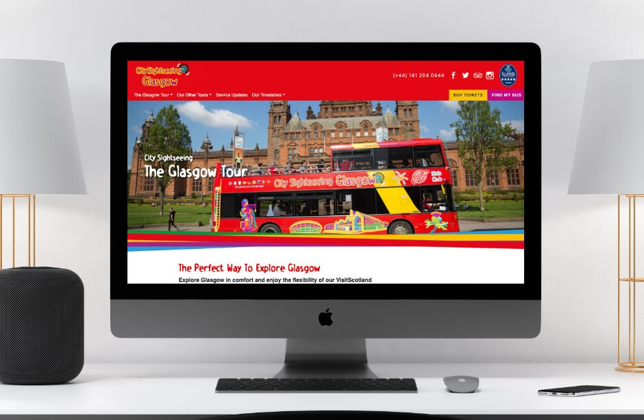 space grey Mac on desk with City Sightseeing Glasgow website open in browser