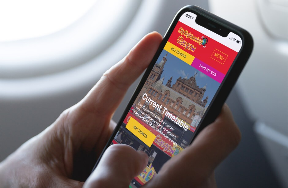 Man holding iPhone on plane with City Sightseeing Glasgow website on screen